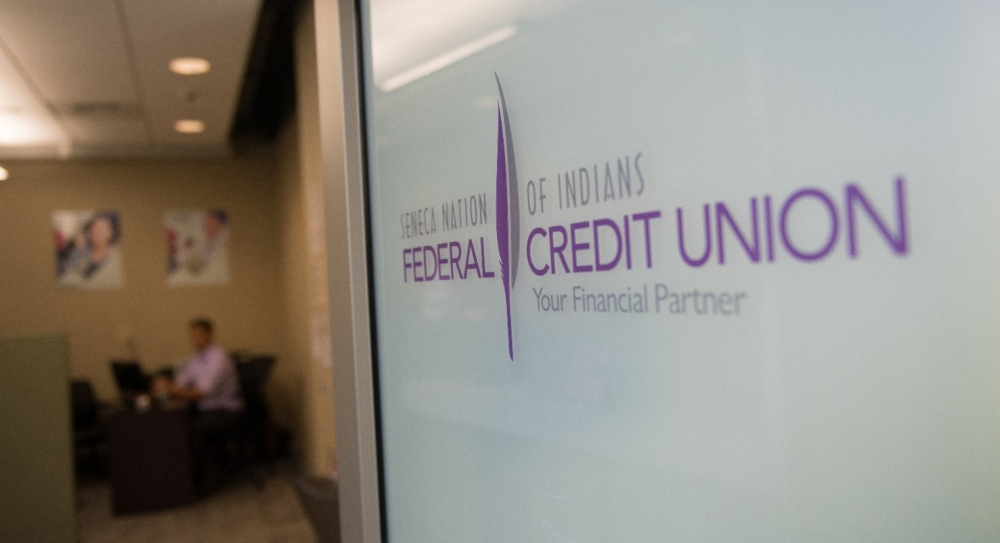 A front door of a credit union is open to show the inside of the office.