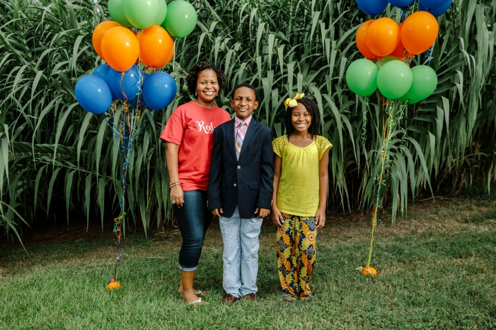 A family stands outside with balloons and poses for a picture.