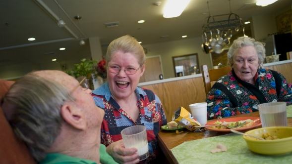 A caregiver laughs with elderly patients.