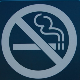 A no smoking sign outside the entrance to a parking lot.