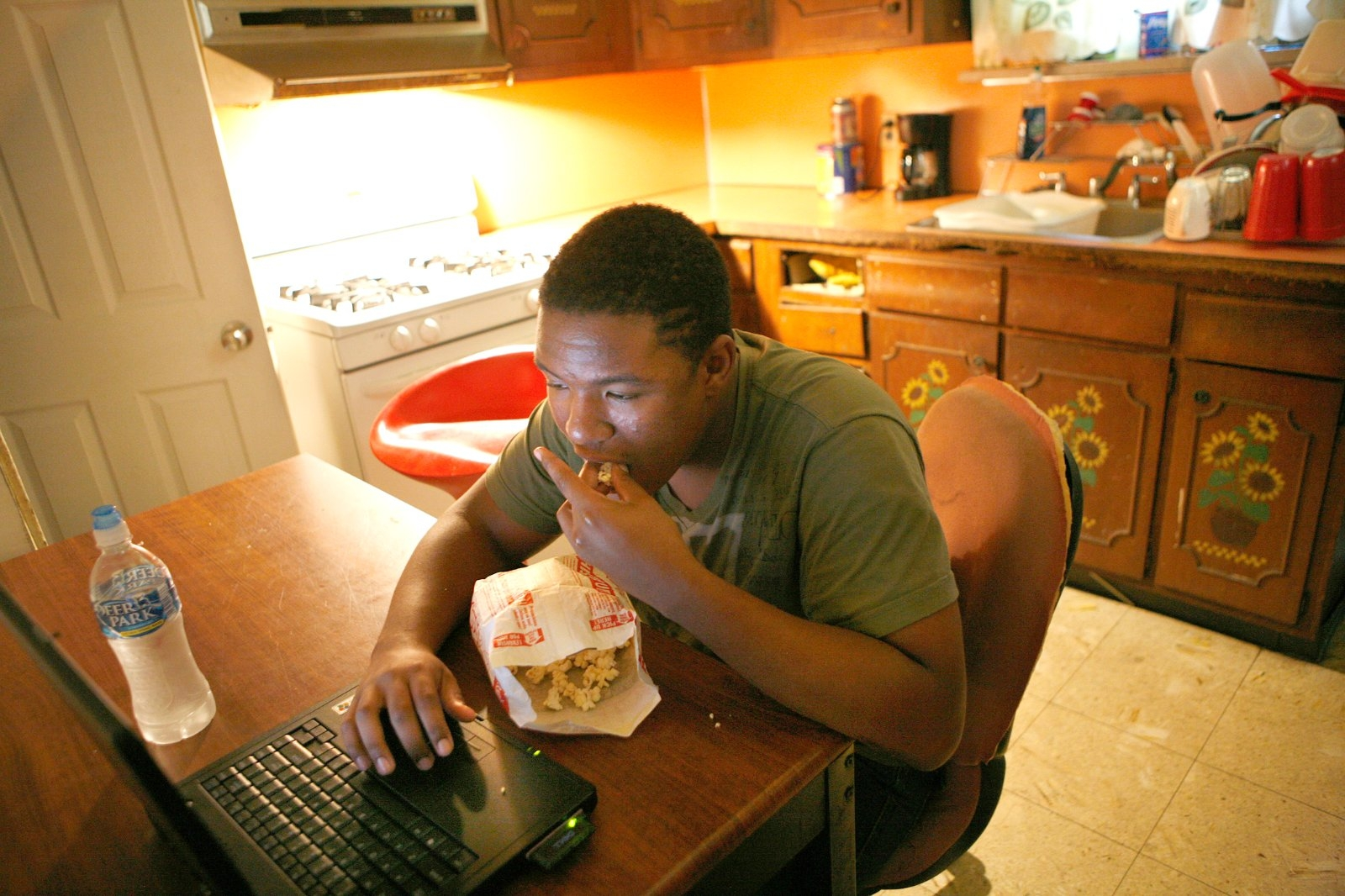 A teenage boy eats popcorn as he works on a laptop.