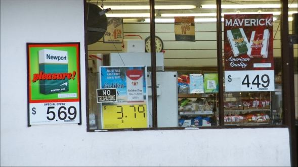 A window in a convenience store with posters advertising cigarettes.
