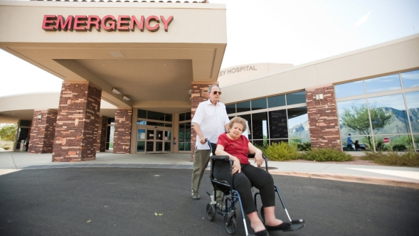 An elderly man wheels his wheelchair bound wife away from a hospital emergency wing.