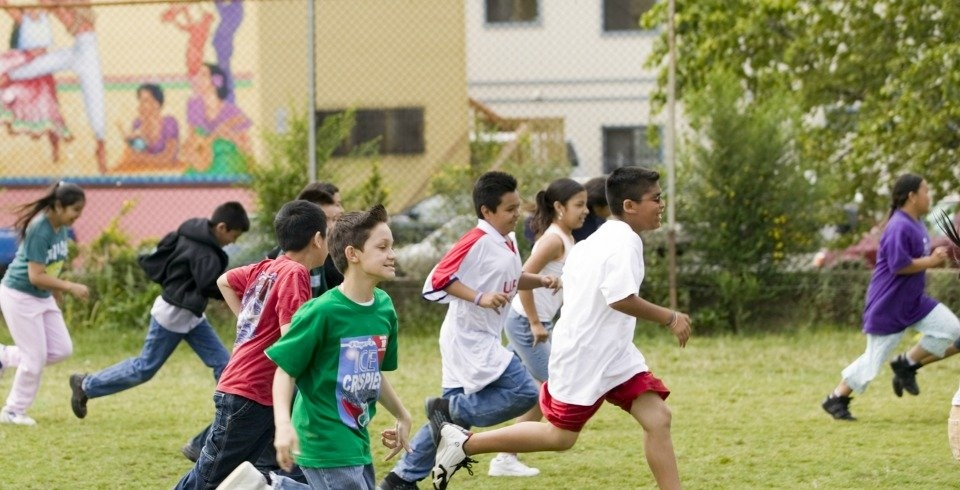 Students running in a race over a school field.