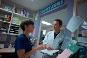 A hospital nurse and doctor confer in an office.