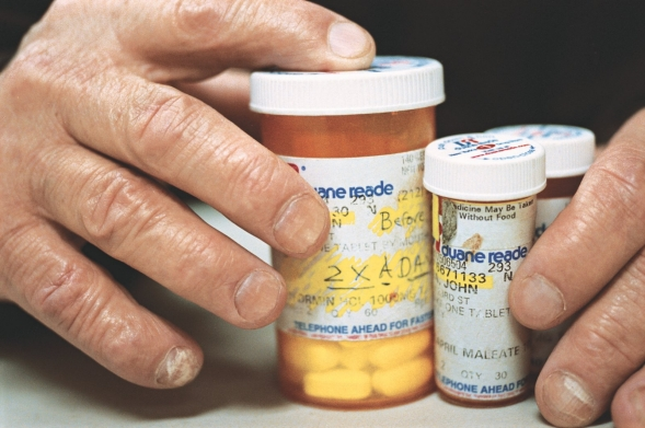 A patient holds a variety of medicine bottles