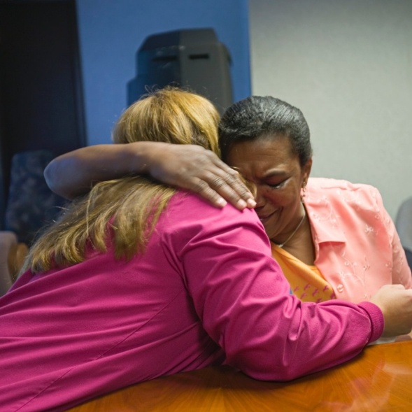 A distressed patient hugs a medical assistant during a meeting.