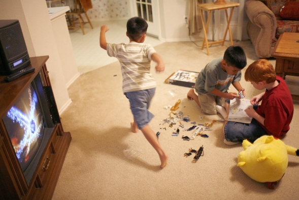 Two boys playing with toys in a living room, another is running out of room.