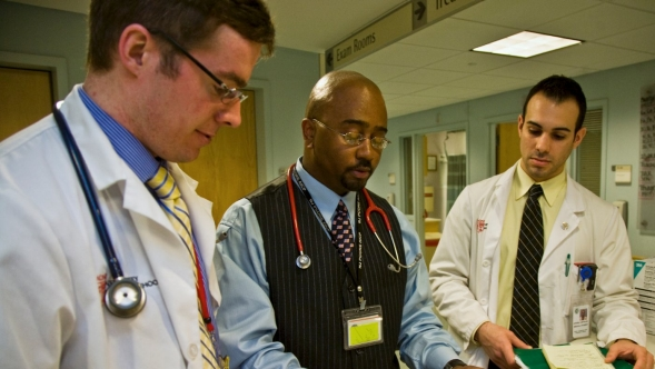 A doctor discusses patient charts with two residents.