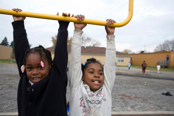 Two girls hanging off a playset in a school yard during recess.