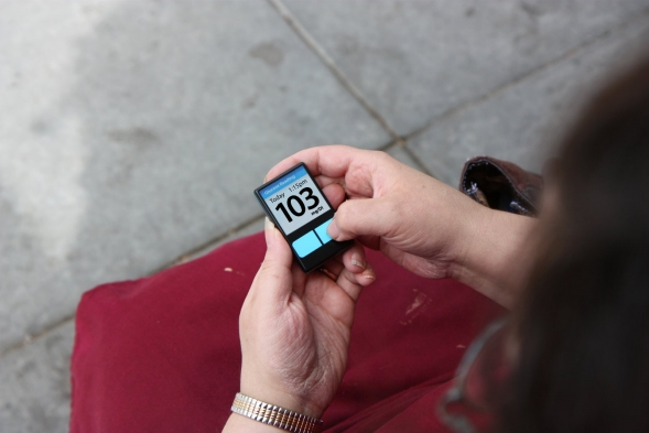 A diabetic woman checks her sugar levels on a glucose meter.