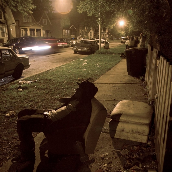 A man sits in an old car seat on the sidewalk of a city residential street at night.