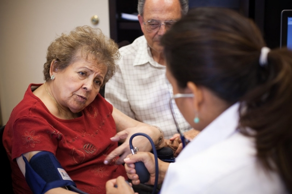 A doctor takes a patient's blood pressure during an office visit.