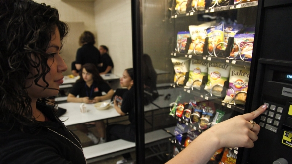 A student buys snacks from a vending machine.
