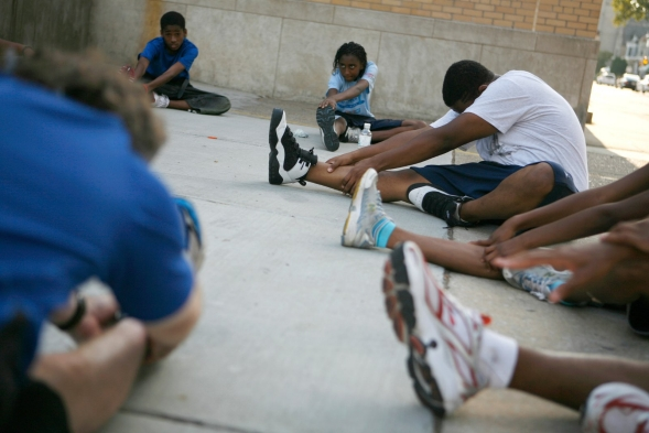 Members of a running club do warm up exercises outside their high school led by their coach.