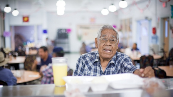 An elderly man collecting a meal in a cafeteria.