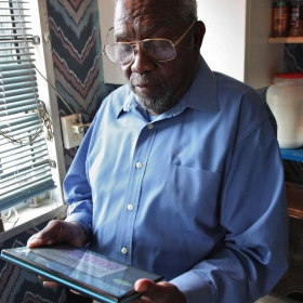 An elderly man using a tablet computer while standing in his kitchen.