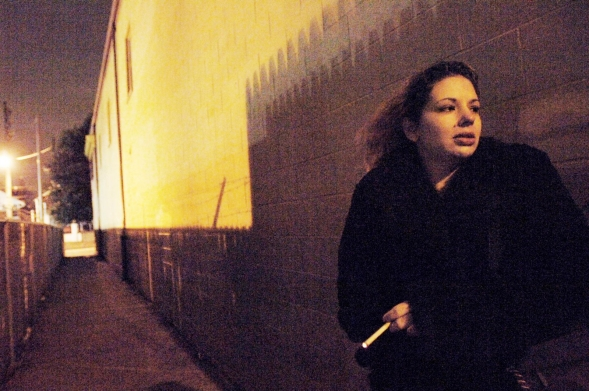 A woman smokes a cigarette outside a building, at dawn.