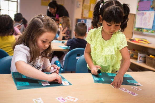 Two preschool girls work on a numbers project in a daycare setting.