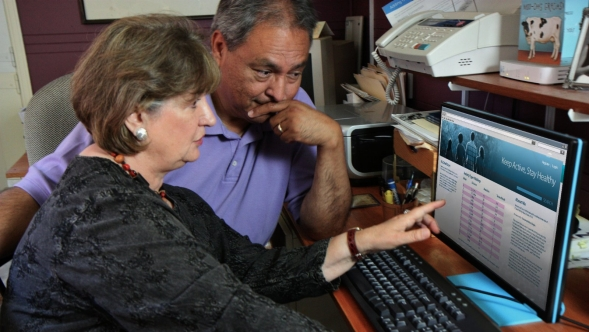 An older man and woman looking at a computer monitor accessing Personal Health Records.