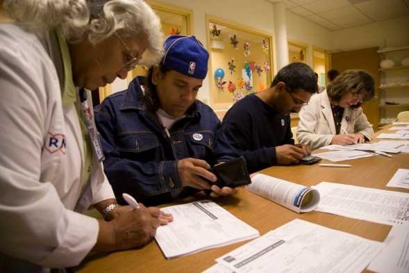 A health worker helps a member of the public complete forms.