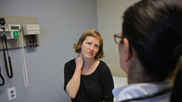 A woman talking to a doctor in an examination room.