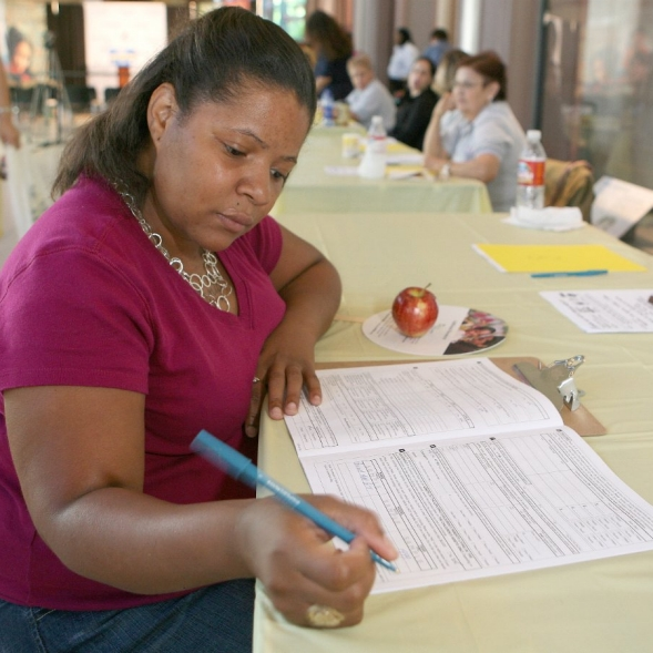 A woman attending an event, sits at a table and completes forms.