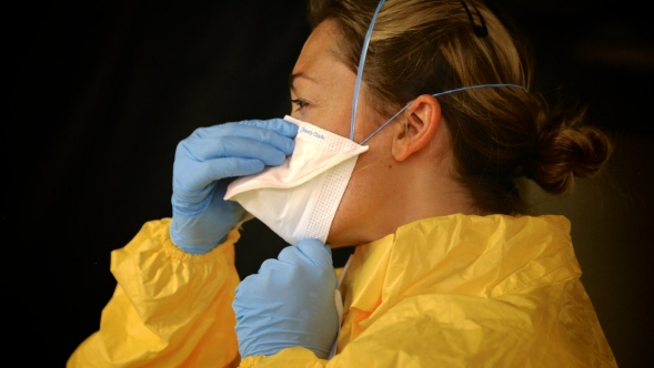 A medical professional dons protective gear during the Ebola outbreak.