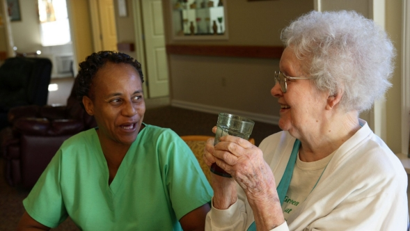 At a nursing home, a nurses' aide sits with a senior who is drinking a glass of water.