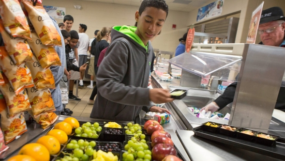 Teenager in school cafeteria chooses healthy lunch.
