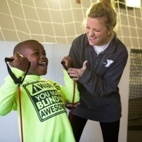 A teacher shows her young student how to use resistance bands for exercise during recess.