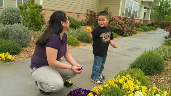 Young woman with young boy outside looking at flowers in a garden.