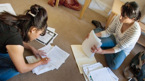 Two women sorting paperwork sitting next to a crawling baby.