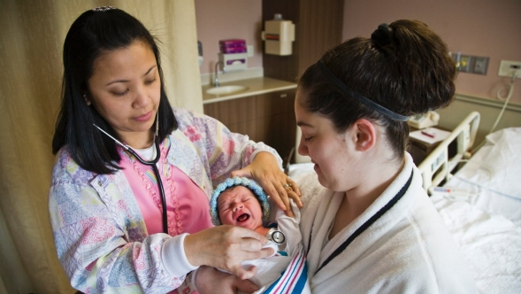 A nurse help a mom with her newborn baby checking vital signs.