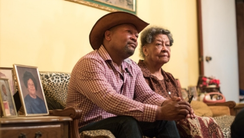 A man sits with his mother in her living room.