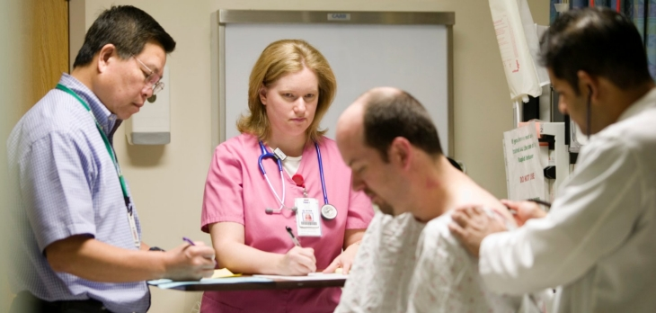Medical professionals check a patient during admittance procedure.