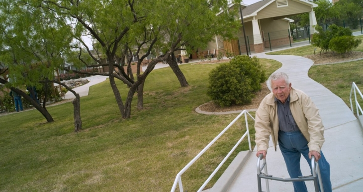 An elderly man walks away from a house, along a path, using a walker.