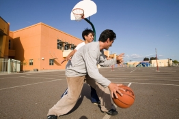 A father and son play basketball on a school yard.