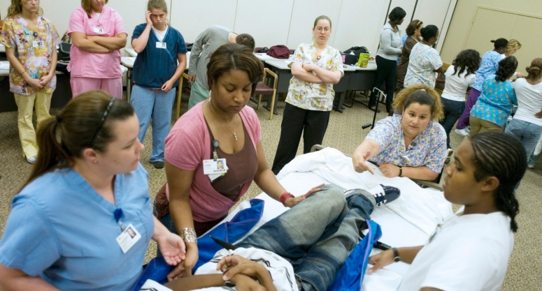 Nursing students in a program learning to transfer a patient from a bed.