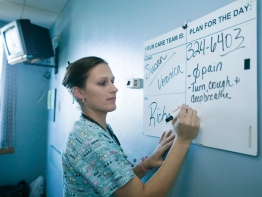 A nurse updates information on a white board in a hospital patient's room.