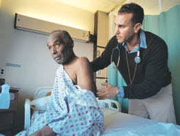 Doctor examines a patient in hospital room