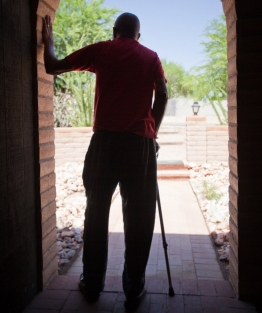 An elderly disabled man walks with a stick on a path in a garden.
