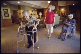 An elderly woman users her walker while watched by her daughter and another older woman.