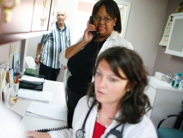 Physicians in a doctor's office, talking on the telephone.