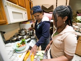 A woman and her teenage daughter prepare vegetables in a kitchen.