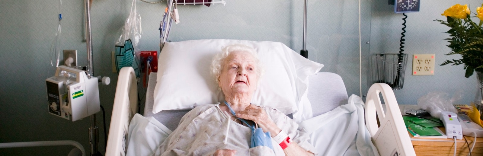 An elderly patient lying in a hospital bed.