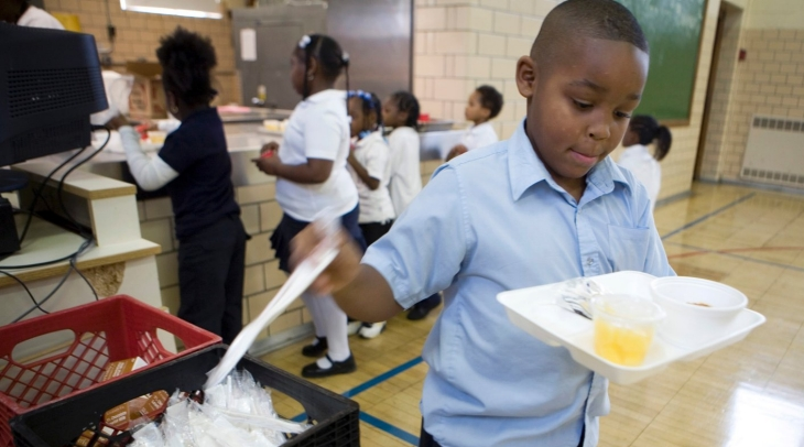 An elementary school student takes plastic cutlery for the meal he is holding.