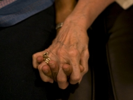 Two people, one elderly, one younger, holding hands.