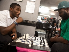 Two young men play chess at a non-profit restaurant.
