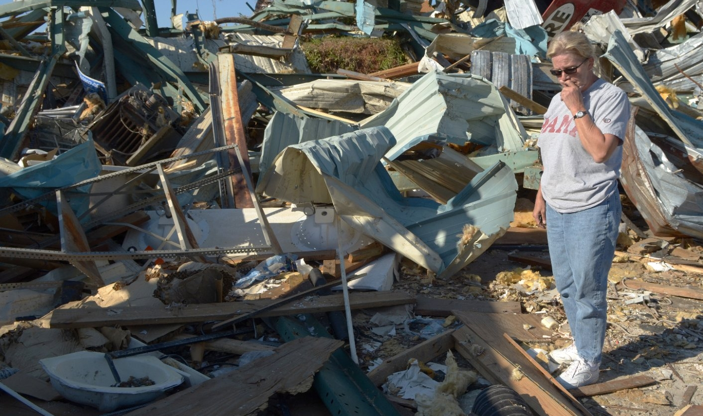 A woman looks at the destruction following a tornado.